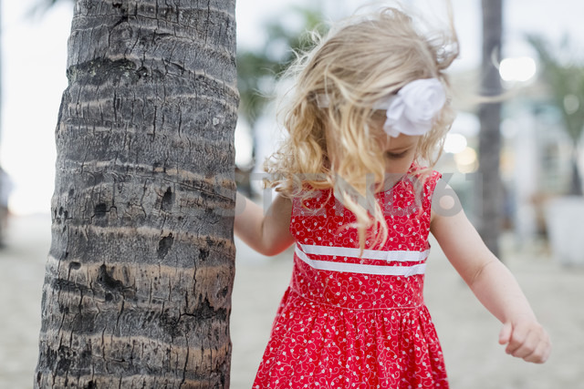 Girl with hair band at palm tree trunk - MAUF000278