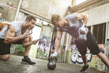 Young man having a workout with kettlebells supported by training partner - MADF000850