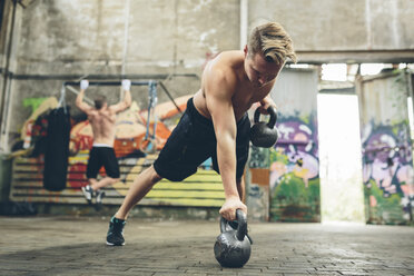 Young man having a workout with kettlebells - MADF000853