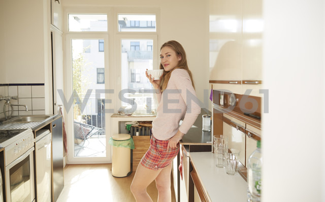 Smiling young woman standing in kitchen with bowl of coffee - FMKF002458 - Jo Kirchherr/Westend61