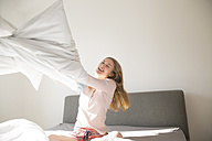 Laughing young woman having pillow fight on bed - FMKF002461