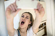 Portrait of young woman pouting mouth while taking selfie with smartphone - FMKF002467