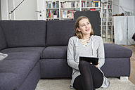 Young woman sitting on the floor of living room with digital tablet - FMKF002470