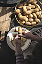 Woman's hands cutting raw potatoes - DEGF000681