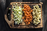 Rows of diced carrot, potato and onion on wooden board - DEGF000693