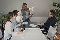 Woman leading a presentation with digital tablet in conference room - PAF001575