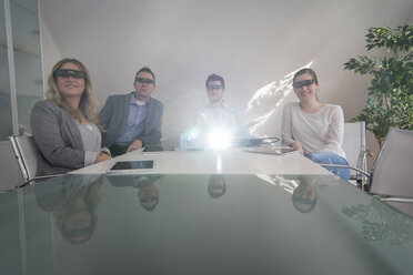 Four colleagues with 3d glasses attending a presentation with projector in conference room - PAF001587
