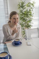 Smiling woman having a coffee break in office - PAF001593