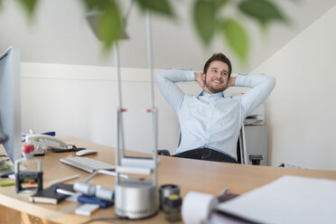 Smiling young man in office leaning back - PAF001602