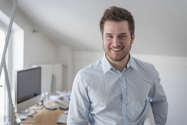 Portrait of smiling young man in office - PAF001605