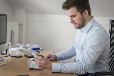Young man at desk in office looking at cell phone - PAF001611
