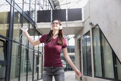 Portrait of young woman listening music with smartphone and headphones - FMKF002486