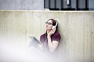 Portrait of young woman listening music with digital tablet and headphones - FMKF002489