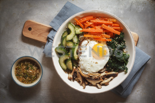 Vegetarian korean rice bowl with mushroom, spinach, cucumber, carrot and fried egg - EVGF002837