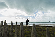 France, Bretagne, Finistere, Crozon peninsula, woman standing at the coast - UUF006698