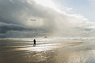 France, Bretagne, Finistere, Crozon peninsula, woman walking on the beach - UUF006710