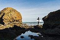 France, Bretagne, Finistere, Crozon peninsula, man standing on rocky beach with surfboard - UUF006728