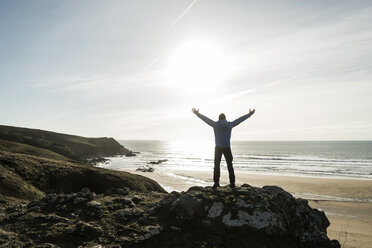France, Bretagne, Finistere, Crozon peninsula, man standing on rock at the coast with outstretched arms - UUF006740