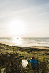 France, Bretagne, Finistere, Crozon peninsula, woman sitting at the coast at sunset with surfboard - UUF006743