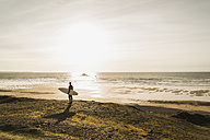 France, Bretagne, Finistere, Crozon peninsula, man standing at the coast at sunset with surfboard - UUF006746