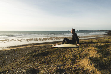 France, Bretagne, Finistere, Crozon peninsula, man sitting at the coast with surfboard - UUF006749
