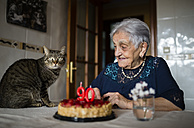 Senior woman celebrating ninetieth birthday with her cat - RAEF000931