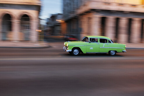 Cuba, Havana, American vintage car driving on a road at twilight - STE000163