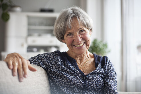 Portrait of happy senior woman sitting on couch at home - RBF004106
