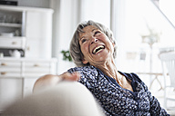 Portrait of happy senior woman sitting on couch at home - RBF004109