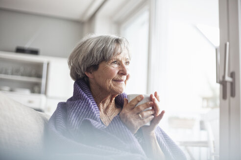 Portrait of happy senior woman sitting on couch at home with cup of coffee - RBF004112