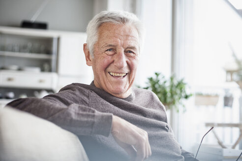 Portrait of happy senior man sitting on couch at home - RBF004115