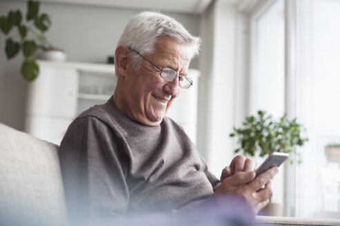 Portrait of smiling senior man sitting on couch at home using smartphone - RBF004118