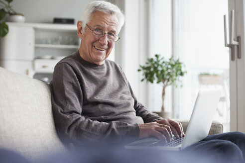 Portrait of smiling senior man sitting on couch at home using laptop - RBF004121