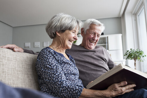 Laughing senior couple sitting on the couch at living room watching photo album - RBF004124