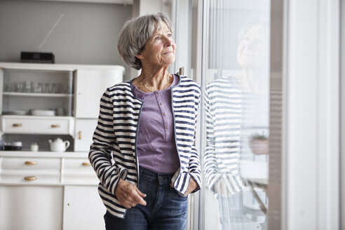 Portrait of senior woman looking through window at home - RBF004145