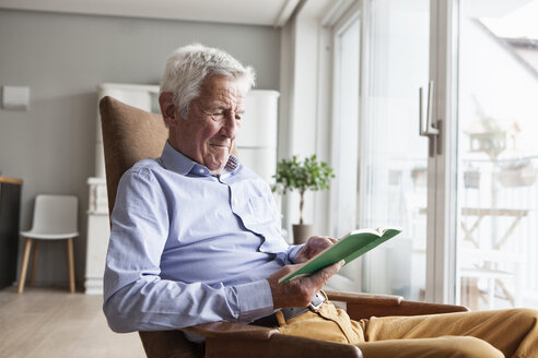 Portrait of senior man sitting on armchair at home reading a book - RBF004154
