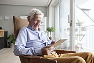 Portrait of happy senior man sitting on armchair at home using digital tablet - RBF004157