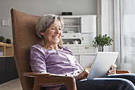 Portrait of senior woman sitting on armchair at home using digital tablet - RBF004166