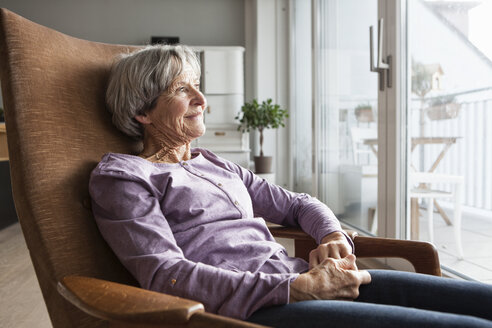 Portrait of senior woman sitting on armchair at home looking through window - RBF004169
