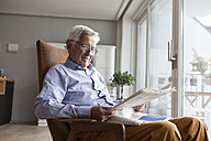 Portrait of senior man sitting on armchair at home reading newspaper - RBF004172