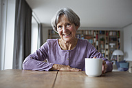 Portrait of senior woman sitting at table with cup of coffee - RBF004175