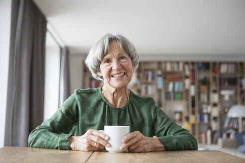 Portrait of smiling senior woman sitting at table with cup of coffee - RBF004178
