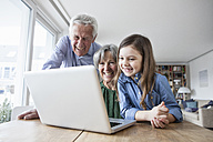 Grandparents and their granddaughter having fun with laptop at home - RBF004190