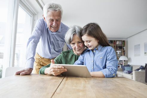Grandparents and their granddaughter looking at digital tablet at home - RBF004193