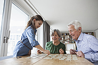 Little girl playing memory with her grandparents at home - RBF004196
