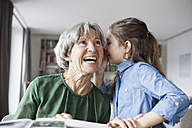 Granddaughter wispering something in the ear of her grandmother - RBF004199