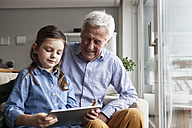 Grandfather and his granddaughter sitting together on the couch using digital tablet - RBF004205