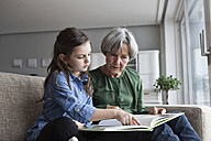 Grandmother and her granddaughter sitting together on the couch with a book - RBF004211