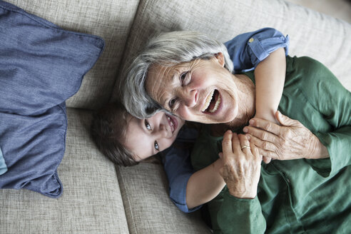 Portrait of laughing grandmother and her granddaughter on the couch - RBF004217