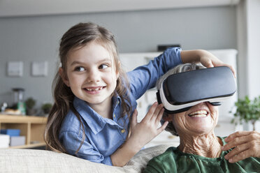 Senior woman and her granddaughter having fun with Virtual Reality Glasses at home - RBF004223
